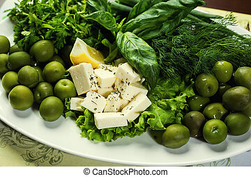 Olives, brynza and greens on a plate, Fresh salad with bryndza, olives, plate of soft cheese (feta and bryndza),Green olives in the bowl