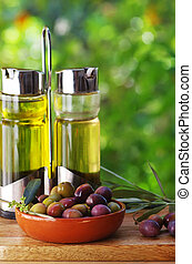 olives fruits and olive oil on green background