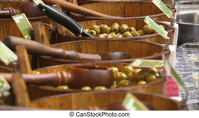 Olives in a supermarket - A steady shot of olives being sold...