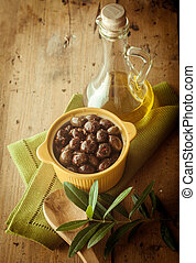 Olives in Dish on Table with Bottle of Olive Oil