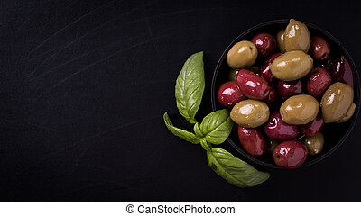 Olives on wooden dark table with basil