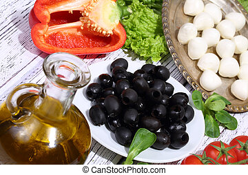 Olives, tomatoes, pepper, a mozzarella and ruccola
