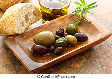 Olives on wooden plate with bread and rosemary