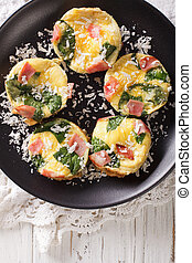 Omelet with spinach, ham and cheese on a plate close-up on the table. vertical top view