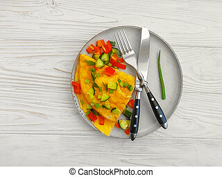 omelet with vegetables on a wooden background