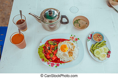 Omelet with vegetables, thai tea and soup on the table