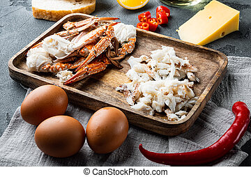 Omelette ingredients with pepper, crab meat, egg, cheese, on gray background