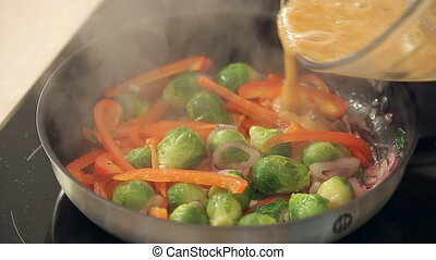 Omelette with Red Paprika, Brussel Sprouts and Onions Frying on a Pan