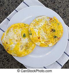 Omelette with vegetables on white plate