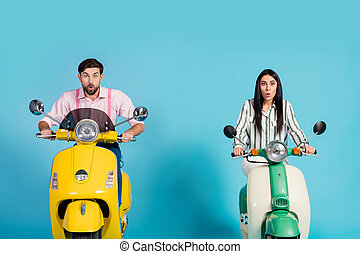 Omg unbelievable. Crazy astonished wife husband drive motor bike look incredible advertisement scream wow omg wear striped pink formalwear shirt isolated over blue color background