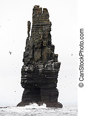 Ominous cliff - Large rock rising out of the sea at the...