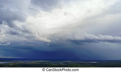 Ominous clouds and distant rains drift across a flat landscape, from an elevated perspective.
