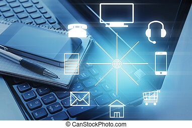 Smartphone and notepad lying on laptop and different icons in circle. Omni channel