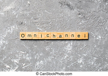 OMNICHANNEL word written on wood block. OMNICHANNEL text on cement table for your desing, concept