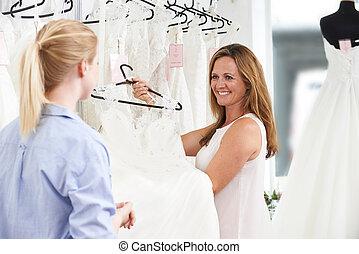 omzet assistent, in, bridal, winkel, portie, bruid, om te kiezen, trouwjurk