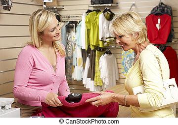 omzet assistent, met, klant, in, de opslag van de kleding