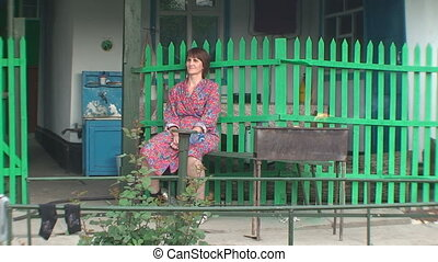 On a bench near the fence sitting woman