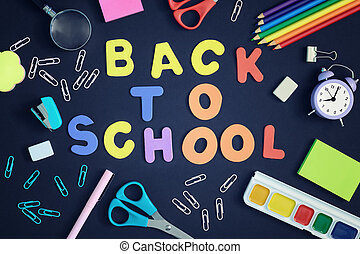 On a black background, school and office supplies are chaotically arranged. In the center is the inscription BACK TO SCHOOL, made in multi-colored letters.