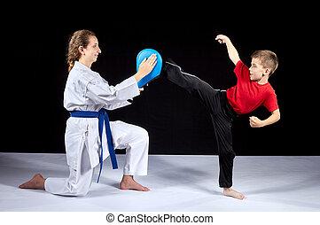 On a black background the boy sportsman beats a kick on the simulator