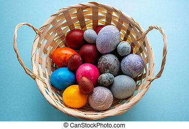 On a blue background, a basket with colorful Easter eggs.The Concept Of Easter