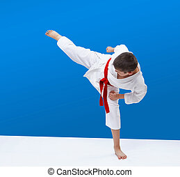 On a blue background boy karate is beating blow leg
