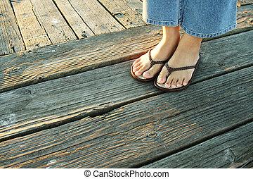 On a boardwalk - A woman\\\'s feet on a boardwalk