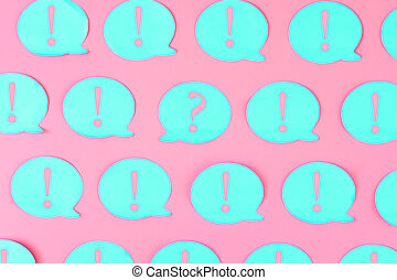 On a bright background are glued blue stickers with pink exclamation marks. In the center is a sticker with a question mark.