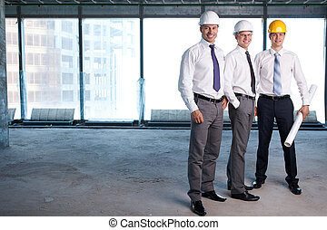 On a construction site - Young men in shirts and helmets on...