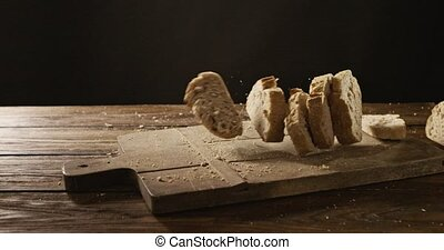 On a cutting board and a wooden table pieces of fresh bread...