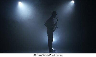 On a dark smoke background young musician playing the saxophone