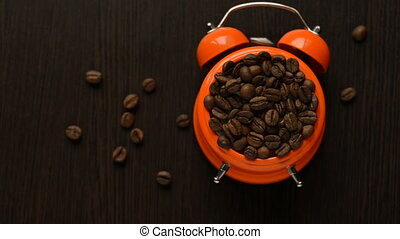 on a dark table, an alarm clock rings with coffee beans falling down
