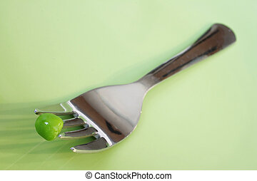 On a Diet - One pea on a fork on a green plate
