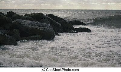 On a group of large stones rolling wave slow motion