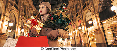 woman with Christmas tree and gift in Galleria Vittorio Emanuele