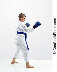 On a light background karateka boy with blue overlays on hands