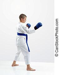 On a light background karateka boy with blue overlays on hands