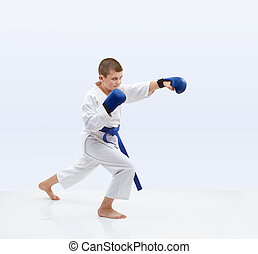On a light background karateka with blue overlays on hands is beating punch