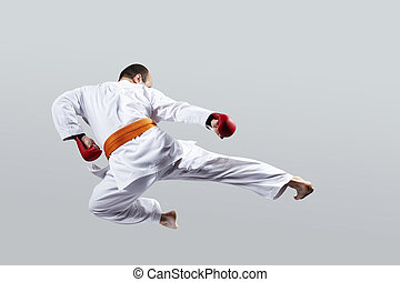 On a light background, the athlete beats a kick in the jump