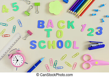 On a light beige background, there are paper clips, a notebook, an alarm clock and school supplies. In the center the inscription in colored letters Back to the School.