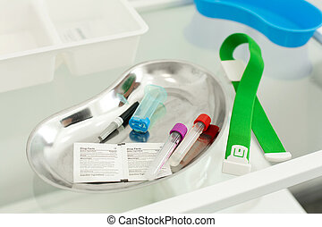 On a metal tray is a set for blood sampling for tests. Harness, test tube, needle