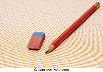 On a millimeter paper there is a simple pencil and an eraser close-up