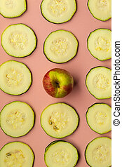 On a pink background there are many round slices of courgette and in the center one small ripe apple
