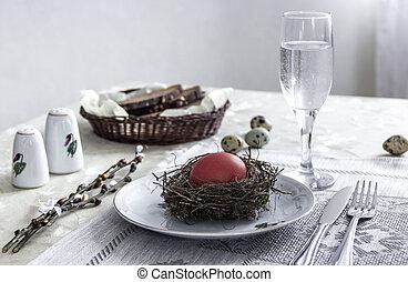 on a plate egg red color fork knife glass of water bread pepper salt nest easter