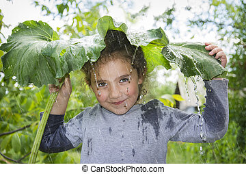 On a rainy summer day, a little girl hides from the rain under a large burdock leaf.