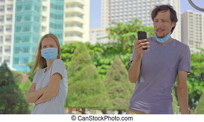 On a street woman and man stand wearing face masks. The man ...