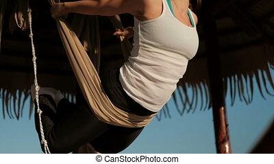 On a sunny beach, a woman swings in a hammock in a flight posture.