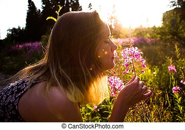 On a sunny meadow among the flowers, on a beautiful sunny, summer and warm day, the girl gets a light touch from the smell of flowers. A light touch keeps the flower and breathes in its delicate fragr