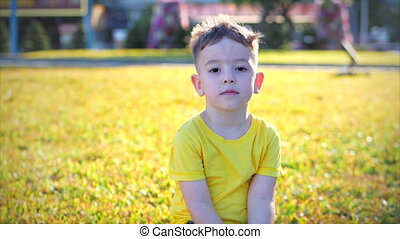 On a sunny summer day, funny little boy looking at camera on the street, cute face of a preschooler child.