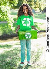 Young environmental activist smiling at the camera holding ...