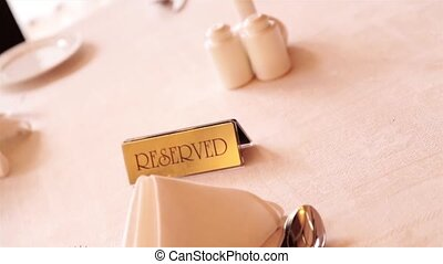 On a table of restaurant with white cloth stands a plaque with the inscription reserved. HD